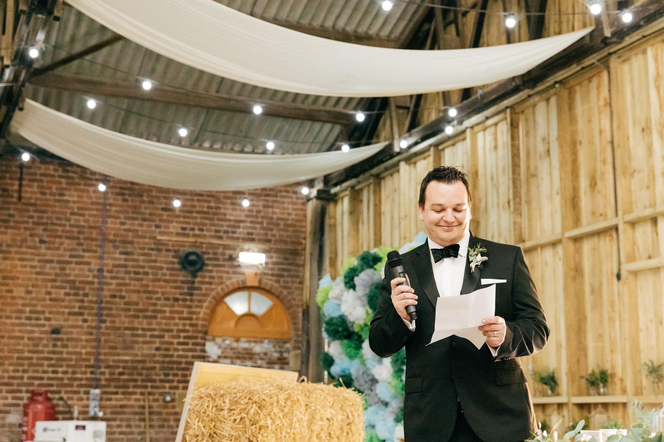 documentary wedding photographer captures speeches at DIY barn wedding