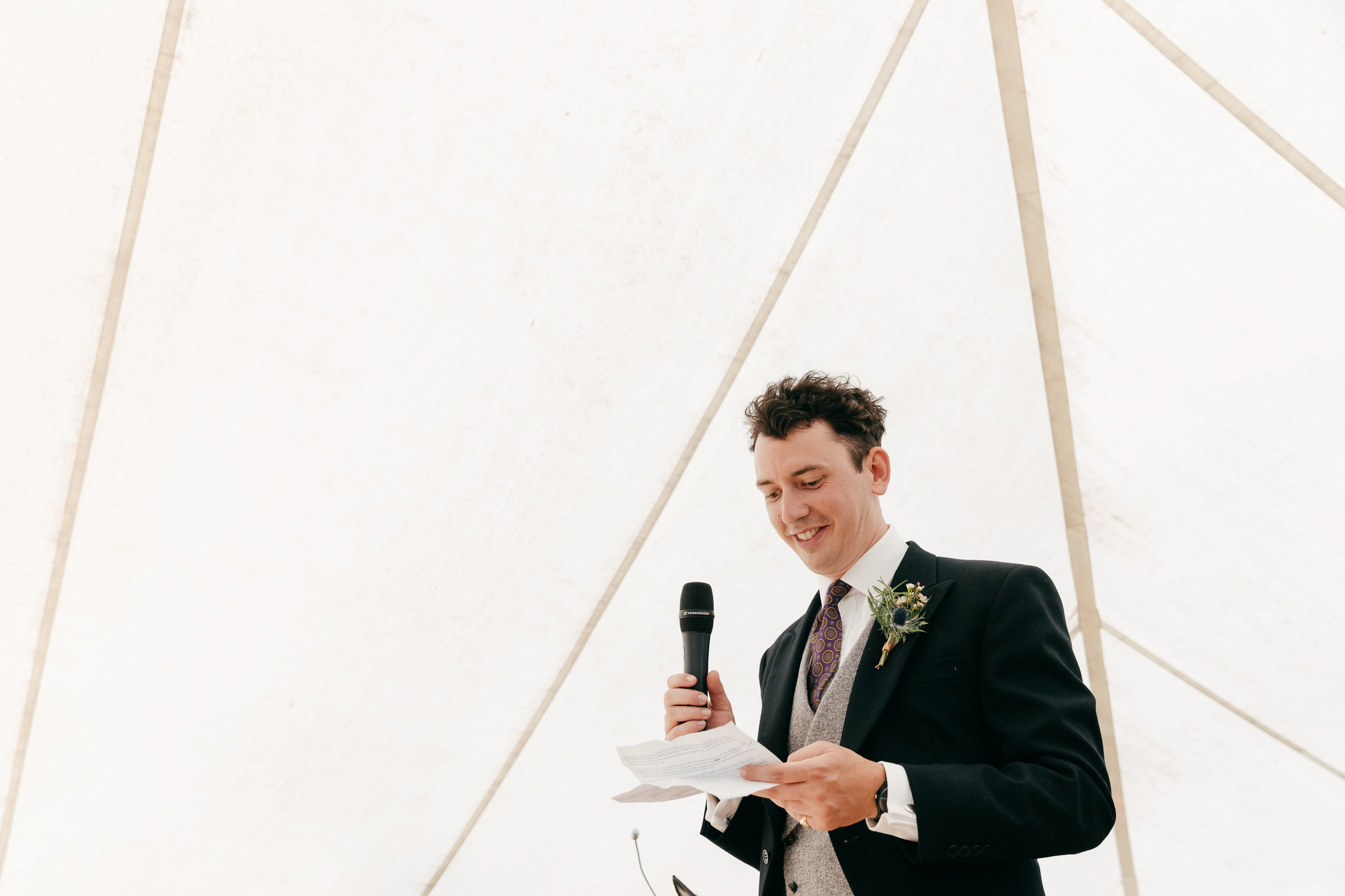 candid portrait of groom giving speech at festival summer wedding
