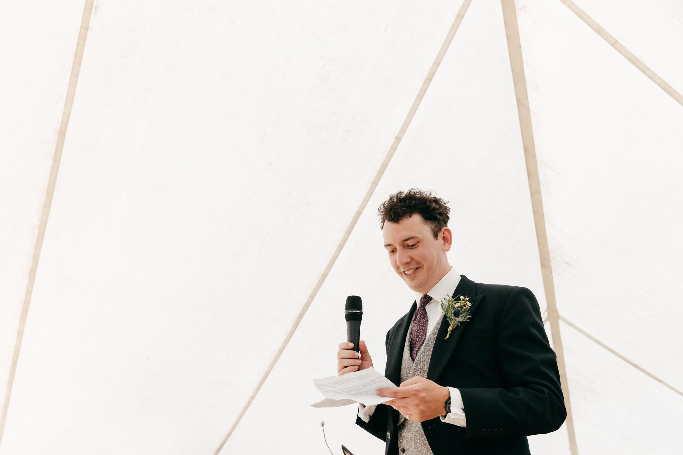 candid portrait of groom giving speech at festival summer wedding