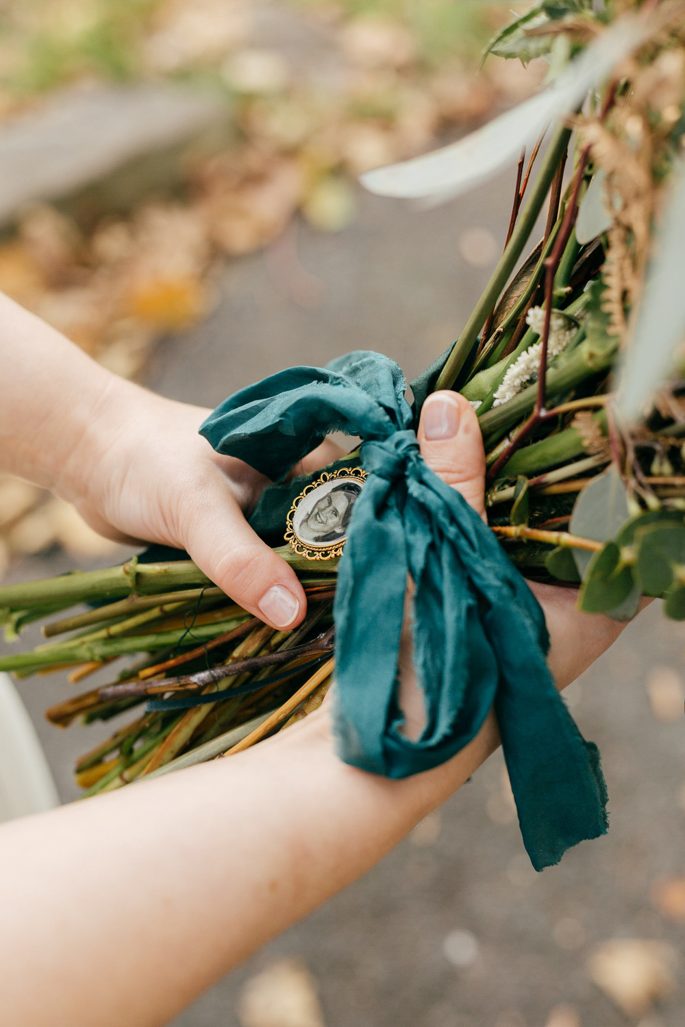 A close up of wedding day details, a broach in the brides bouquet