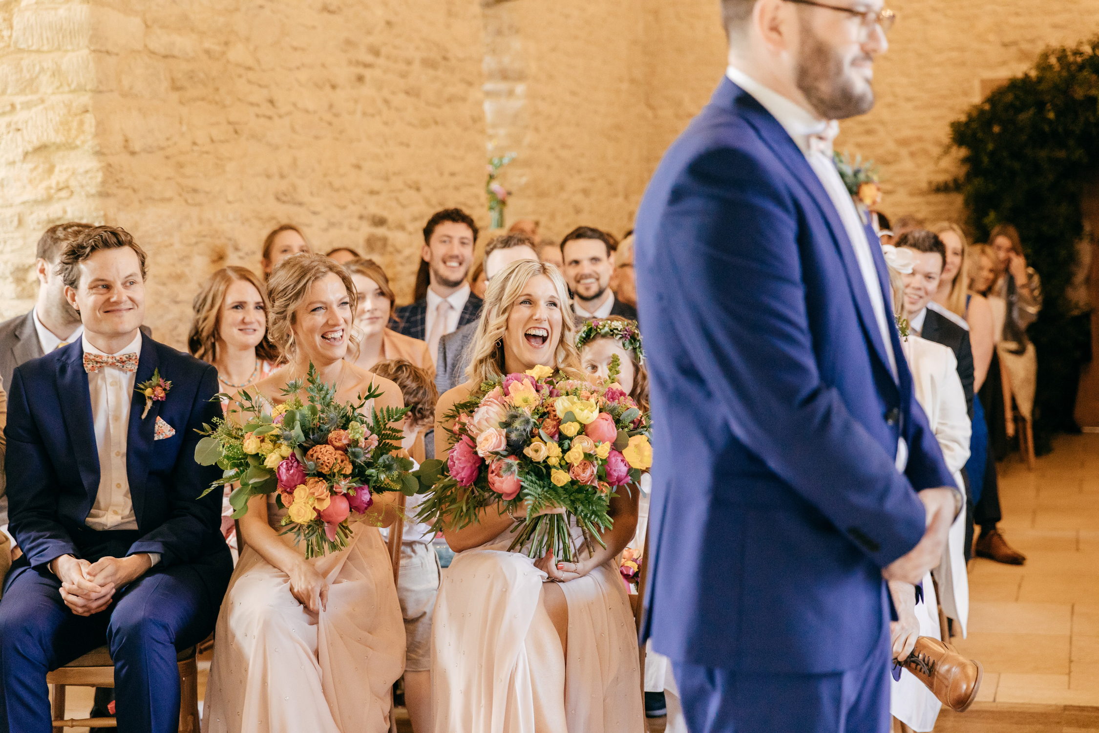 natural wedding photo of guests at kingscote barn and their joyful reaction to couple being officially married