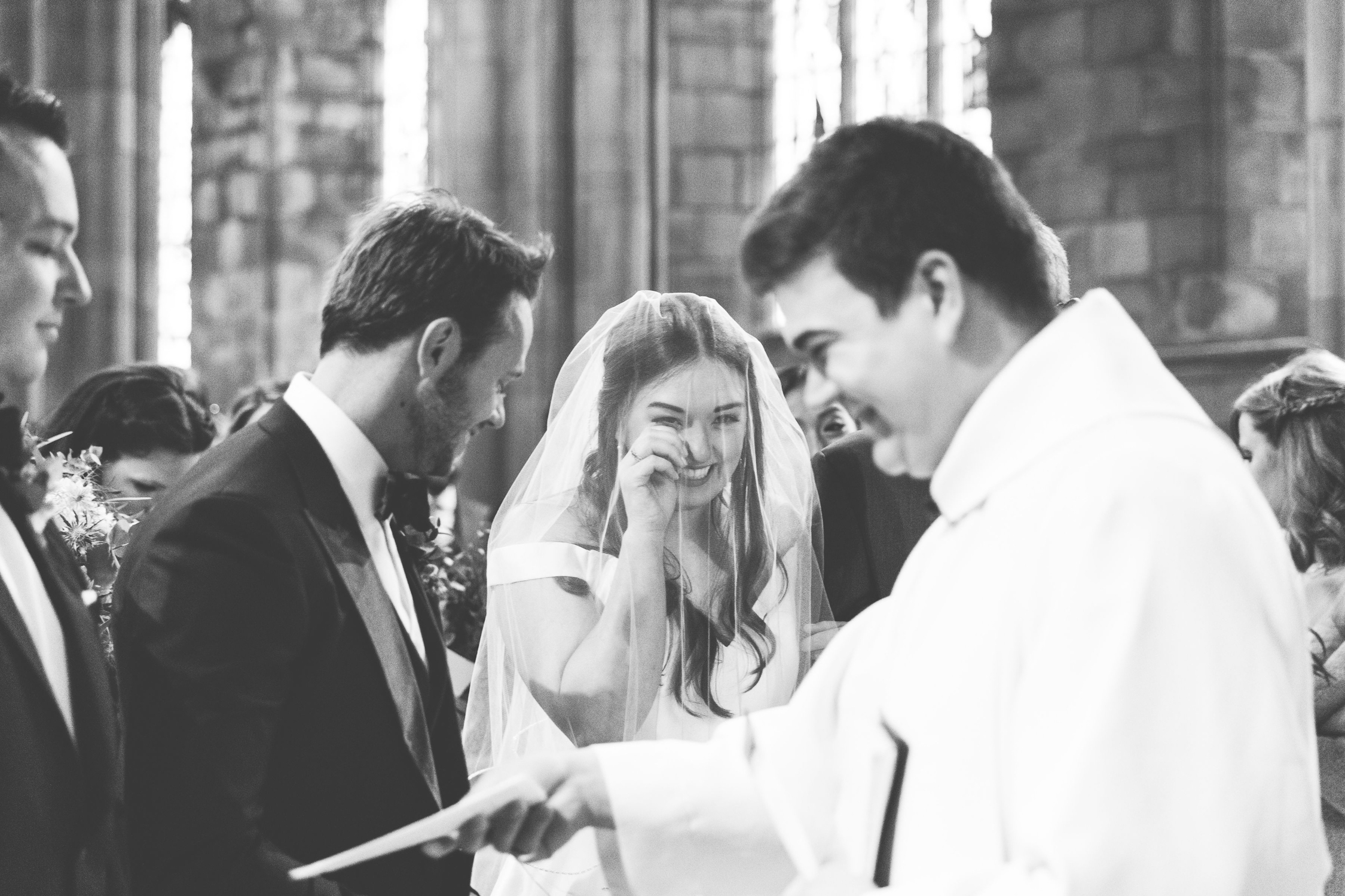 natural wedding photography of bride wiping away joyful tears at during church wedding ceremony
