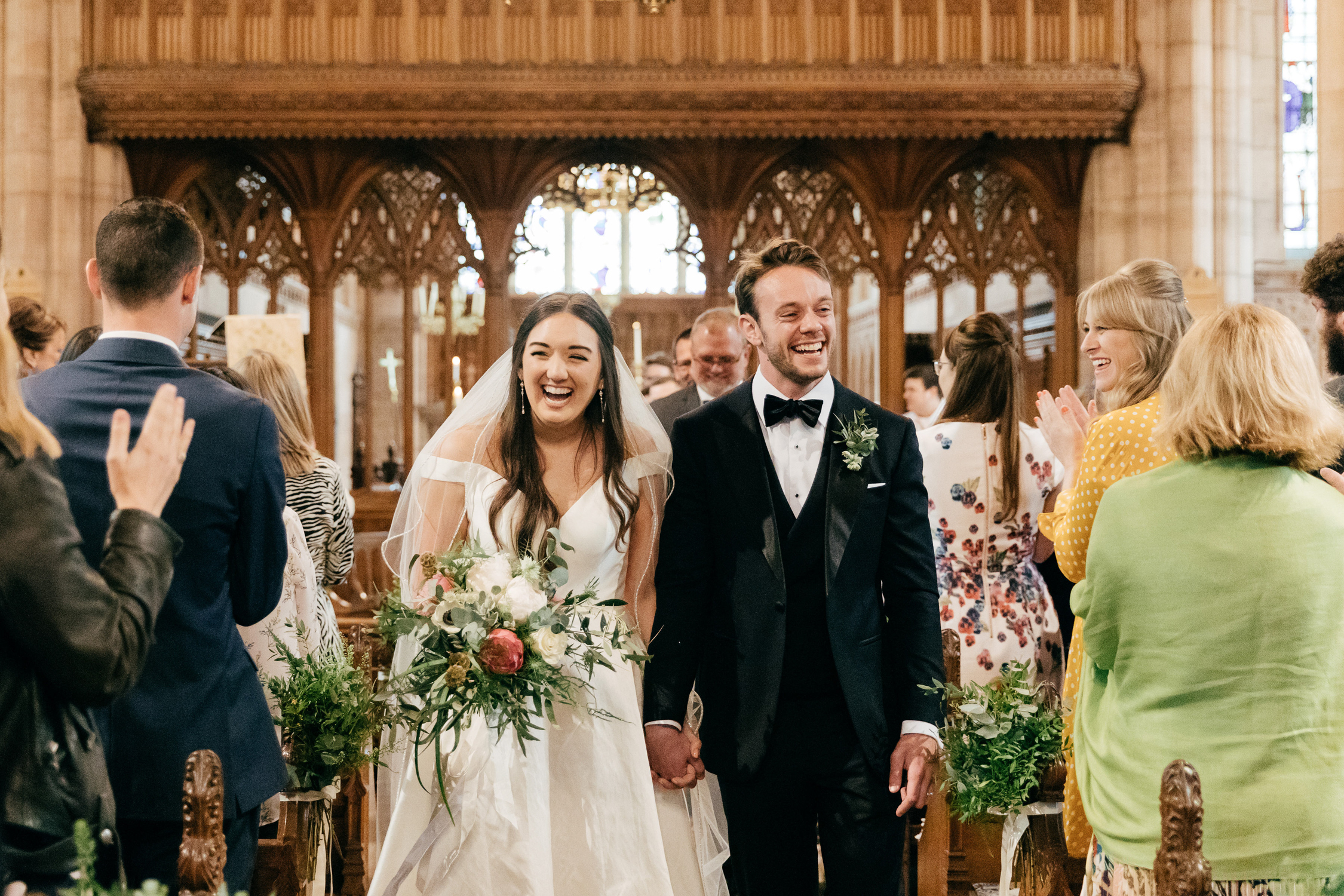 candid wedding photo of happy couple walking down church aisle together at the end of wedding ceremony