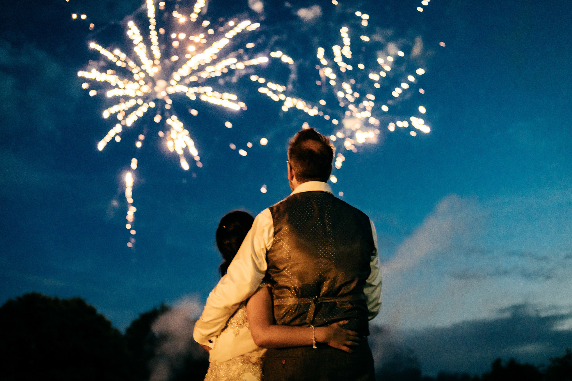 bride and groom embrace and enjoy fireworks finale to wedding reception