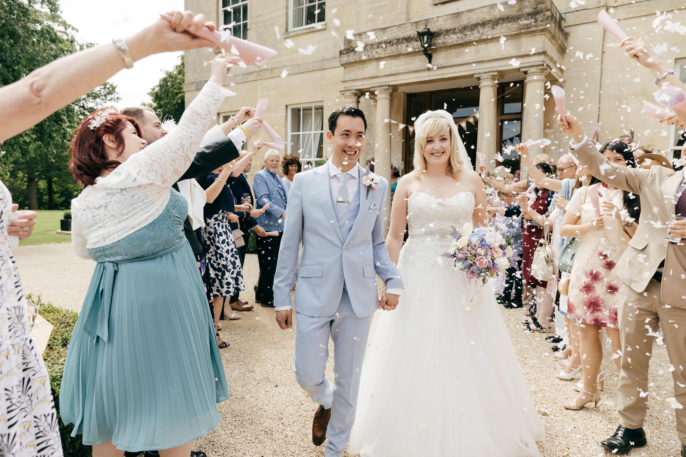 candid photo of joyful couple walking through confetti at pastel themed wedding at eastington park