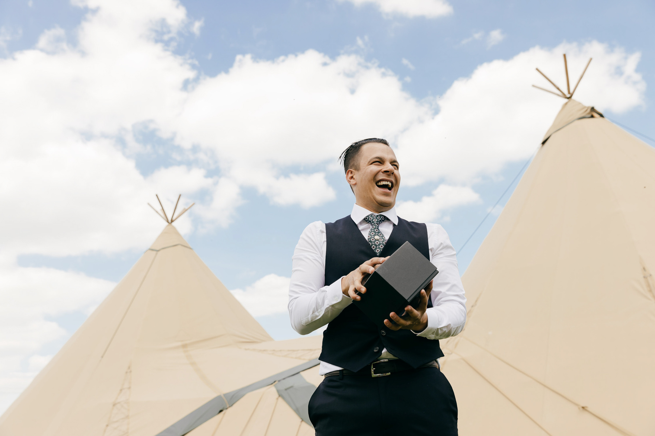 creative wedding photo of groom opening wedding gift in front of tipi backdrop