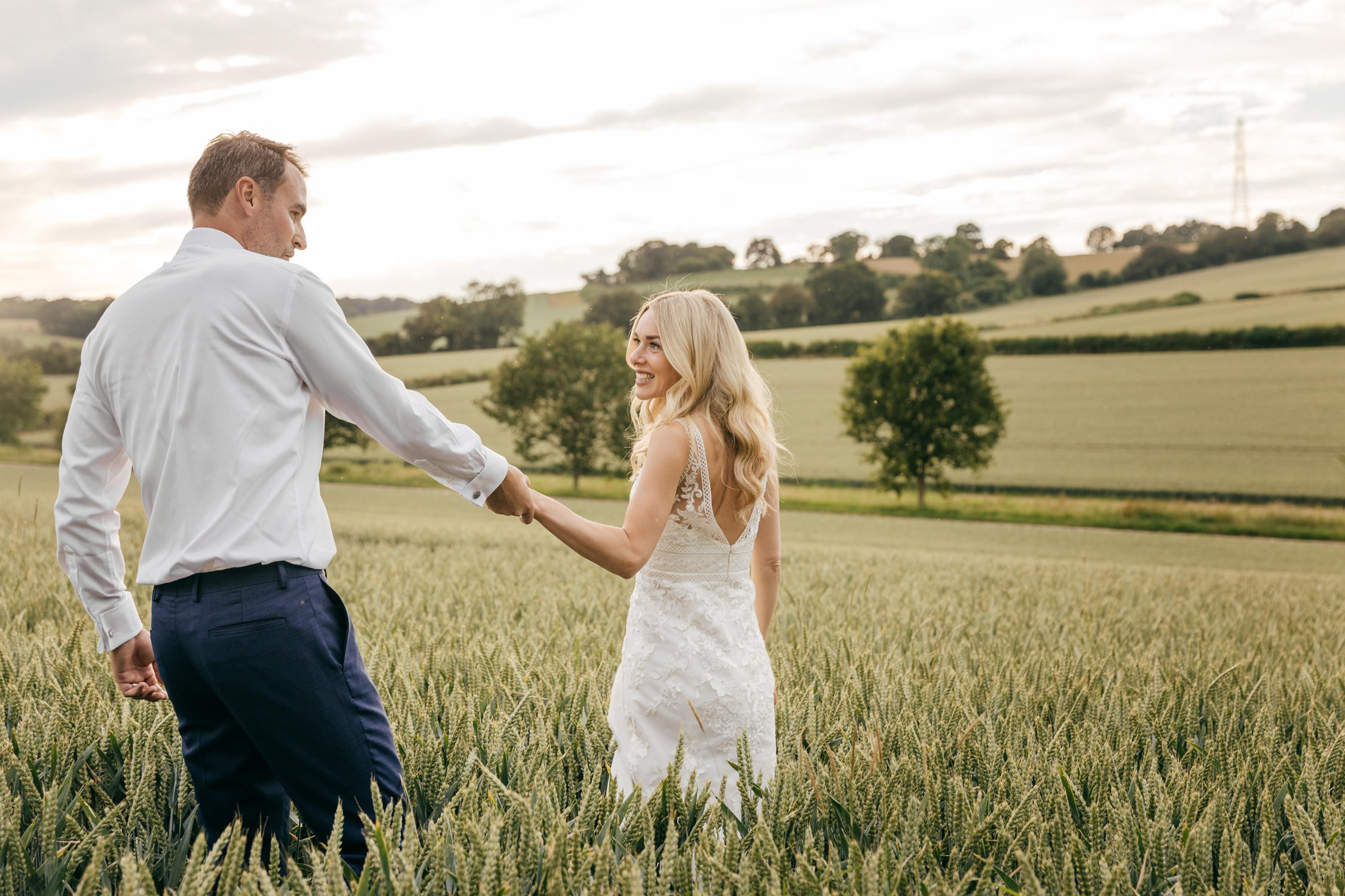 natural portrait of couple taking sunset walk through field on wedding day