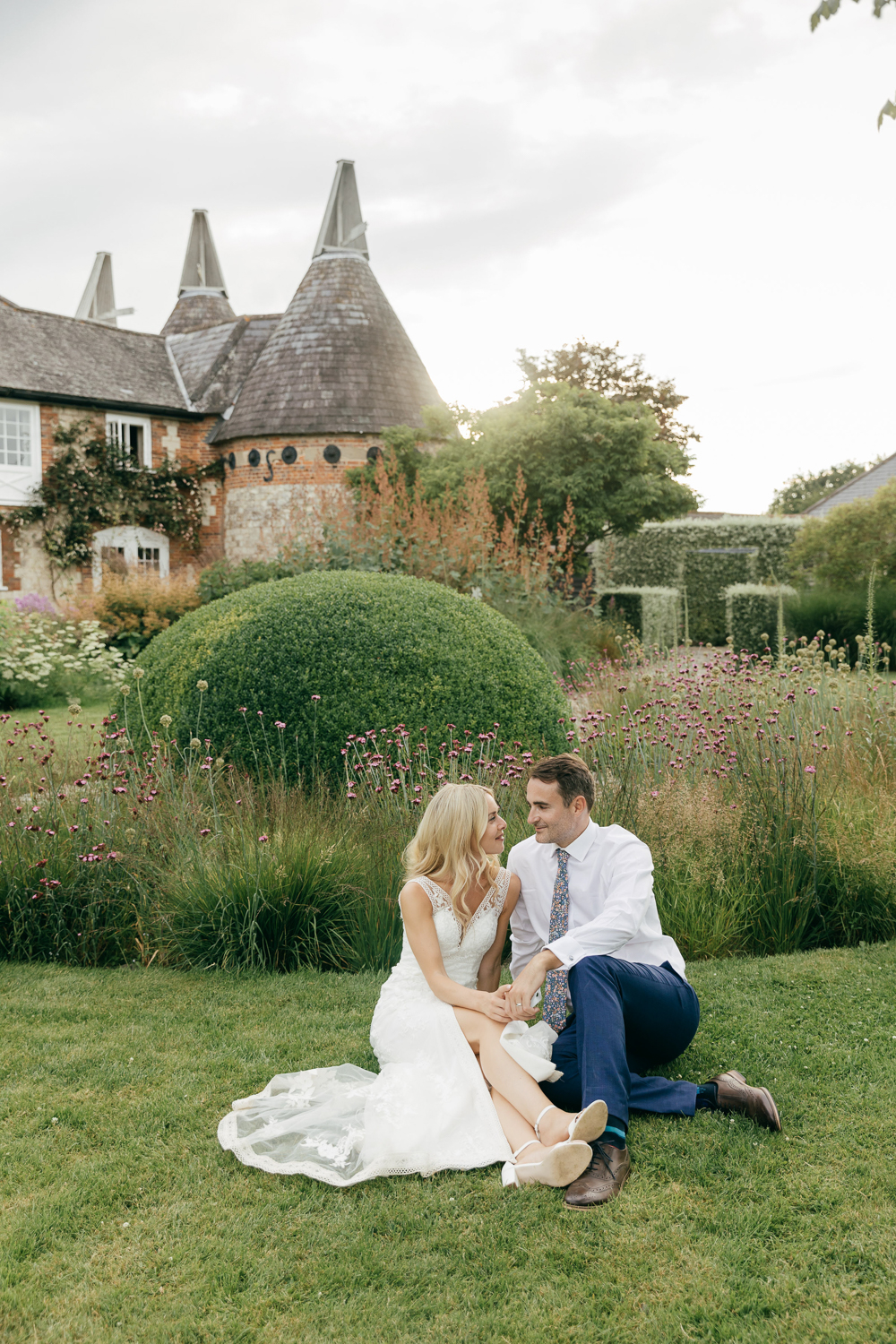 candid photo of bride and groom sat amongst flowers in beautiful garden
