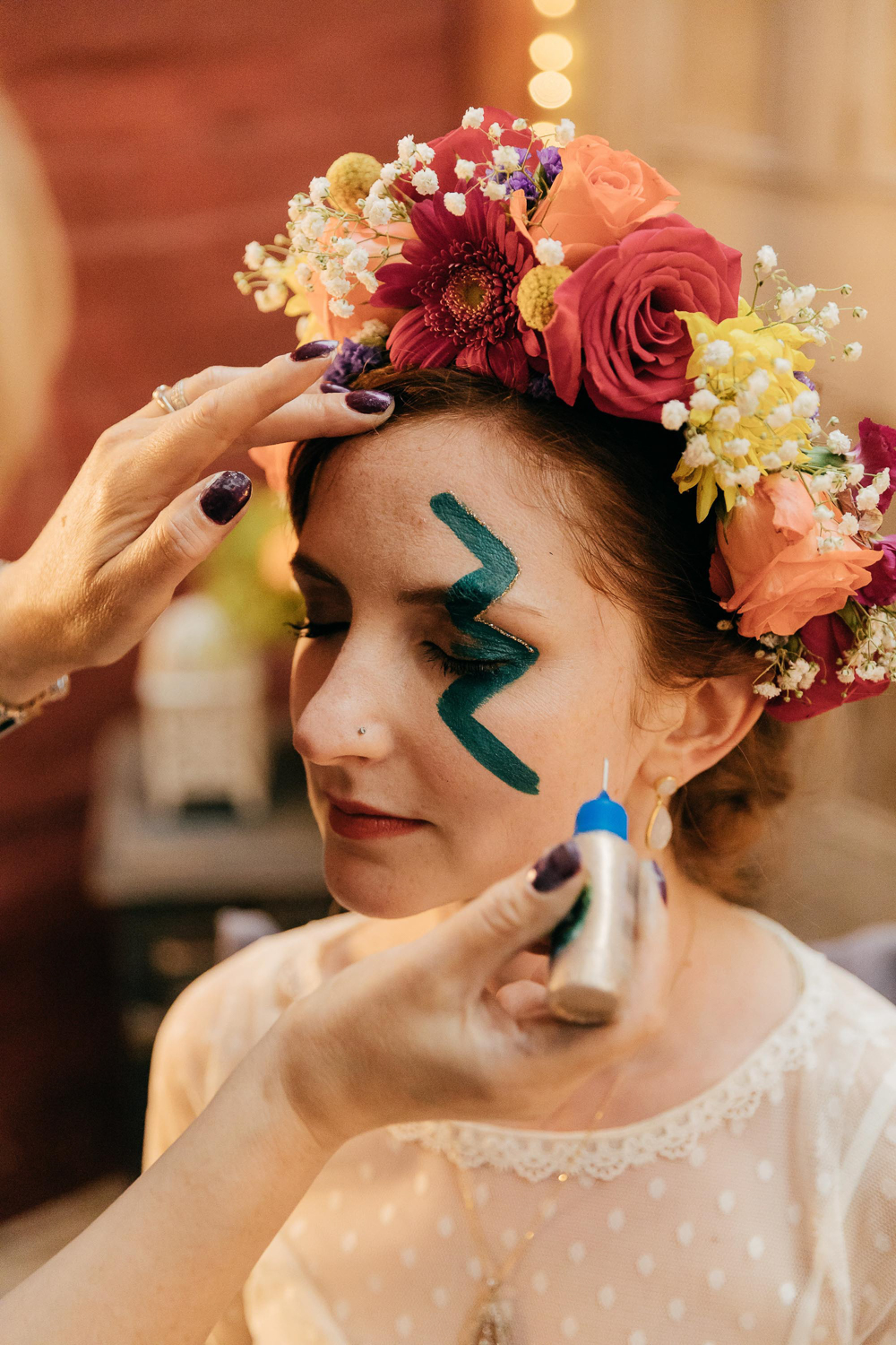 quirky vintage bride has bowie inspired face paint for wedding reception party