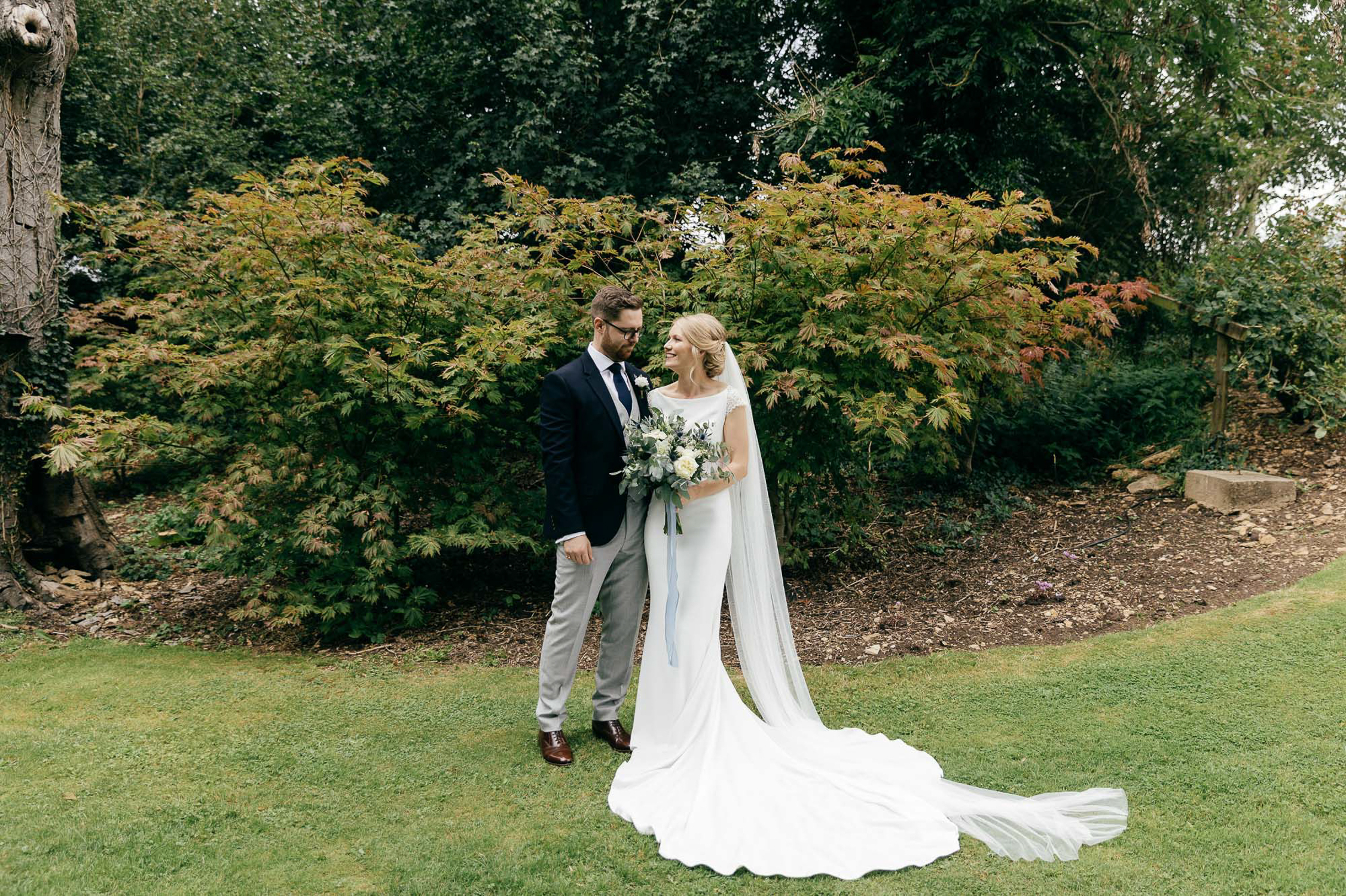 relaxed portrait of bride and groom in gardens of cripps barn