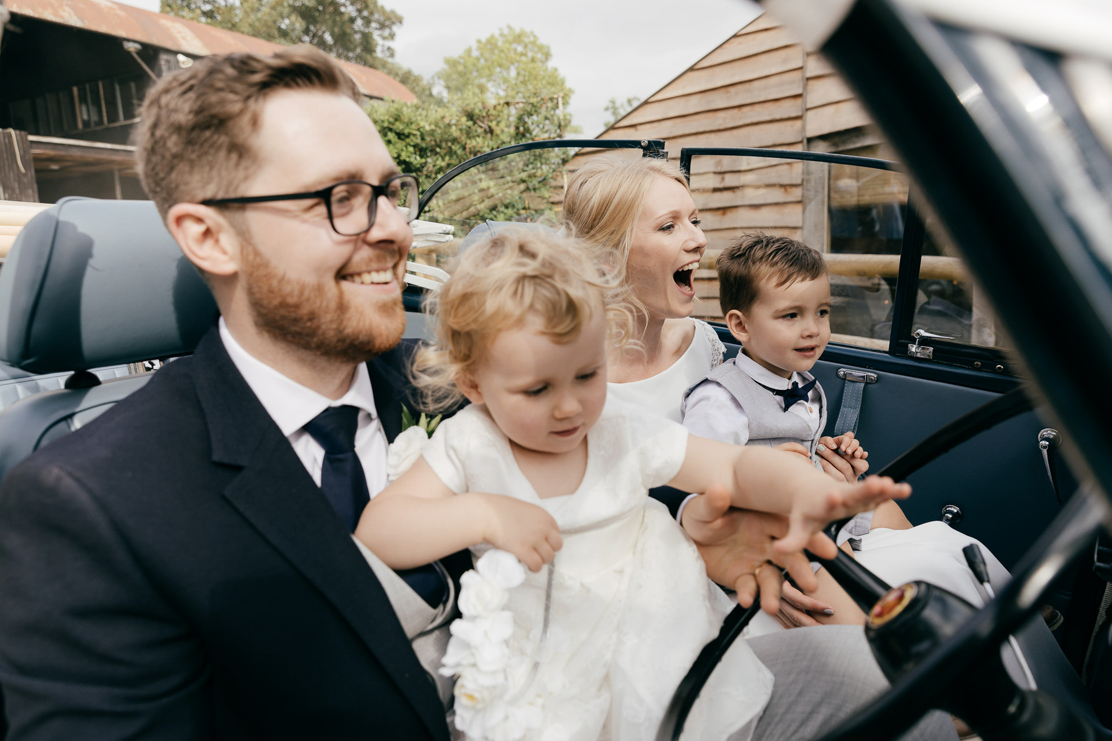 candid photo of bride and groom sat in vintage car with niece and nephew