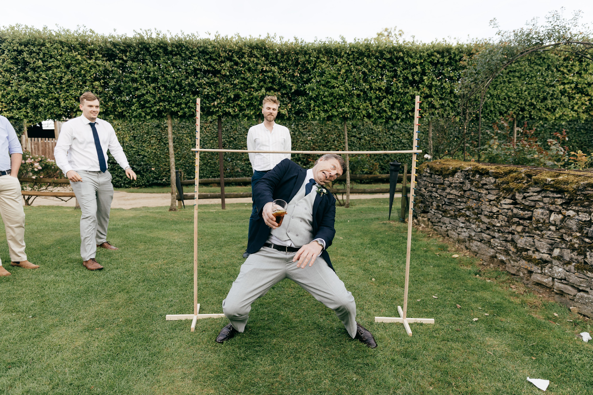 candid and funny photo of wedding guest playing limbo