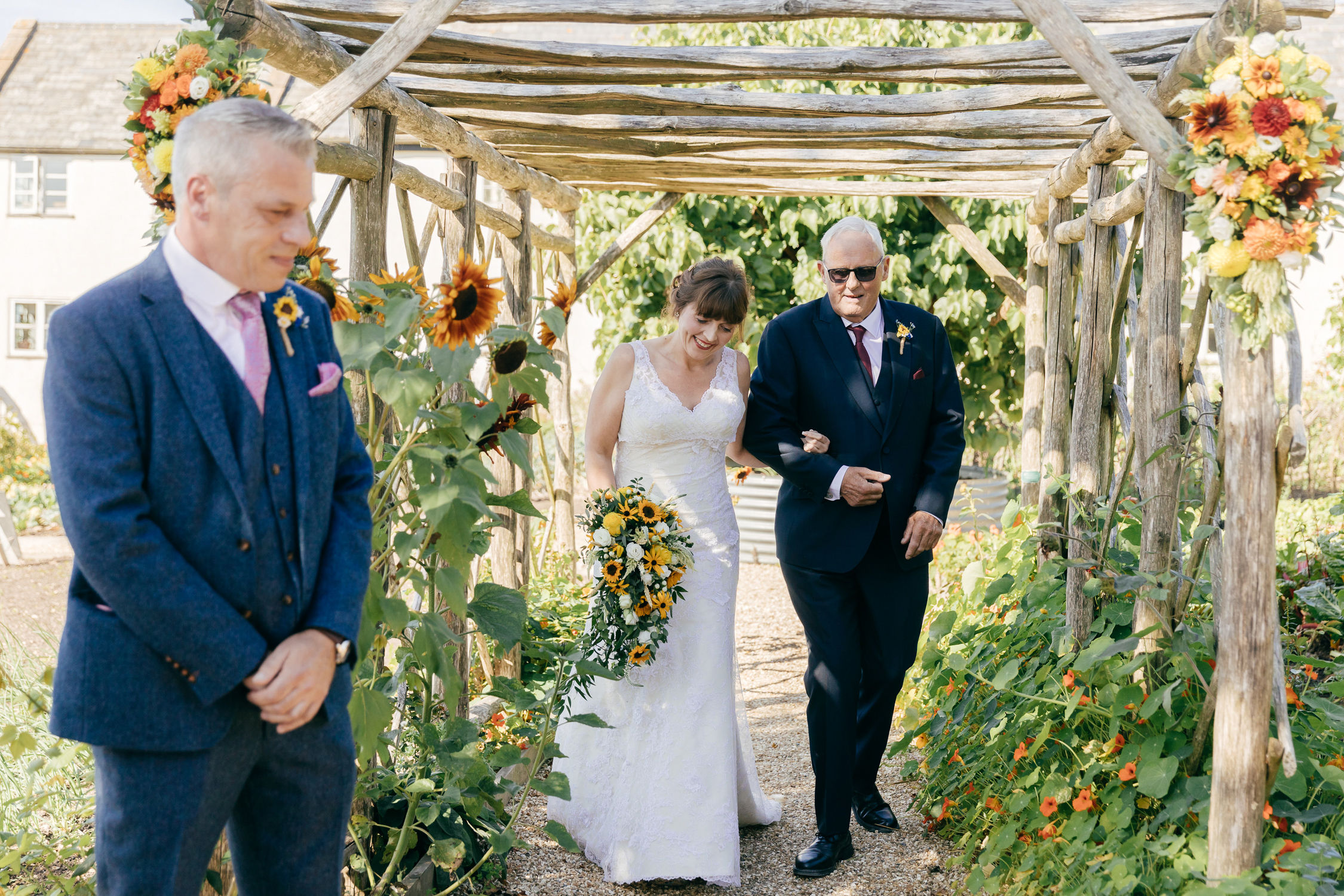 bride walking through flower arch aisle surrounded by sunflowers at outdoor river cottage wedding ceremony
