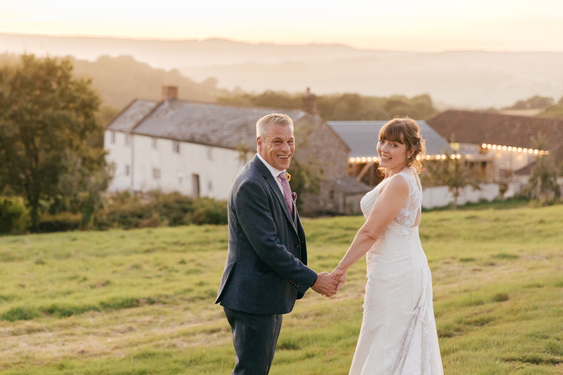 bride and groom walking past river cottage at sunset