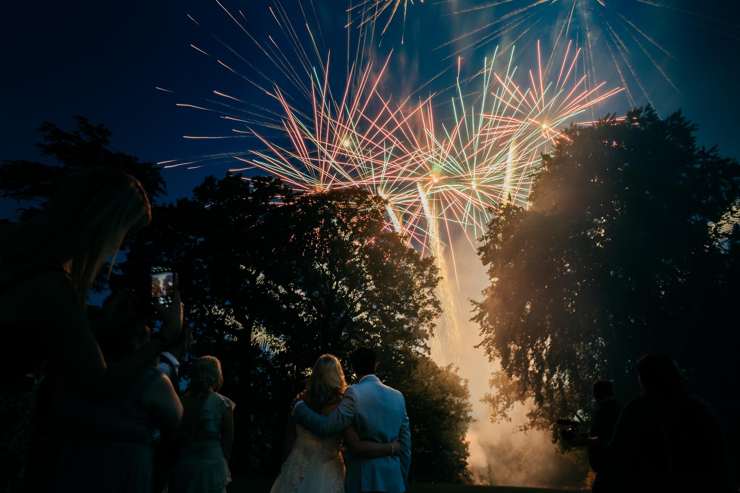 creative portrait of couple watching fireworks at Eastington park wedding