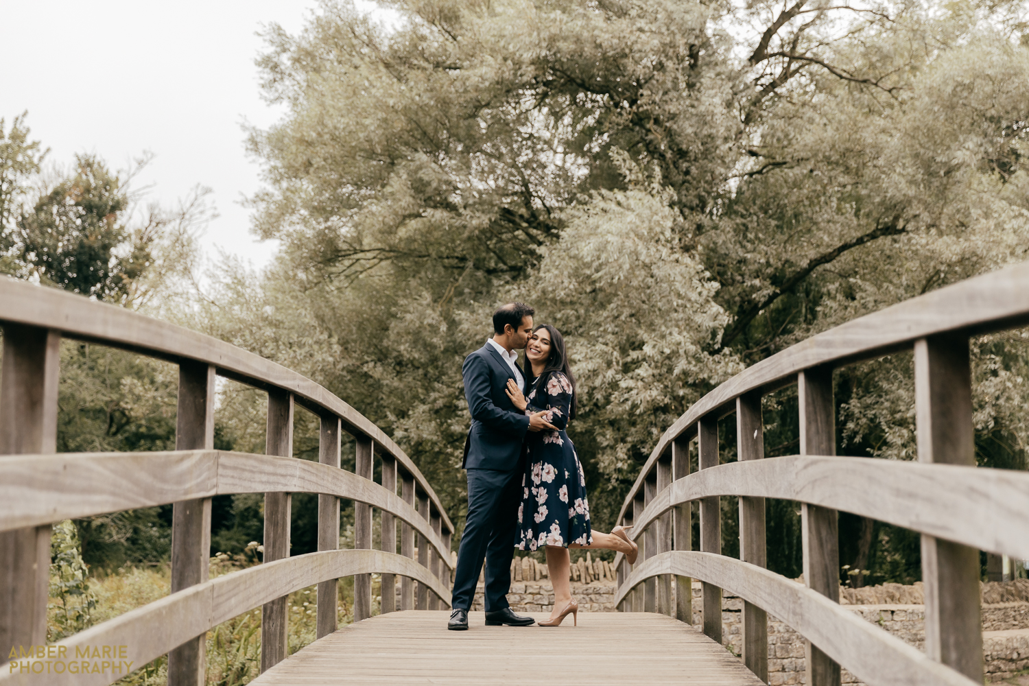 Stylish portrait of bride and groom kissing on a bridge, surrounded by trees in The Cotswolds.