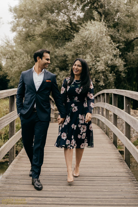 Joyful bride and groom, walking hand in hand across a bridge in The Cotswolds.