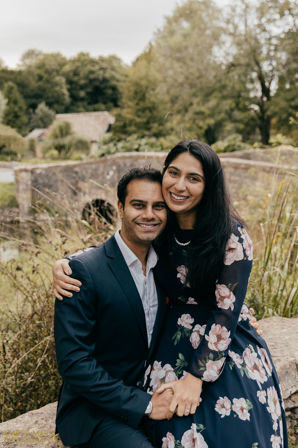 Black bride and groom sat on a wall, in front of a river in a cotswold village. Embracing and smiling.
