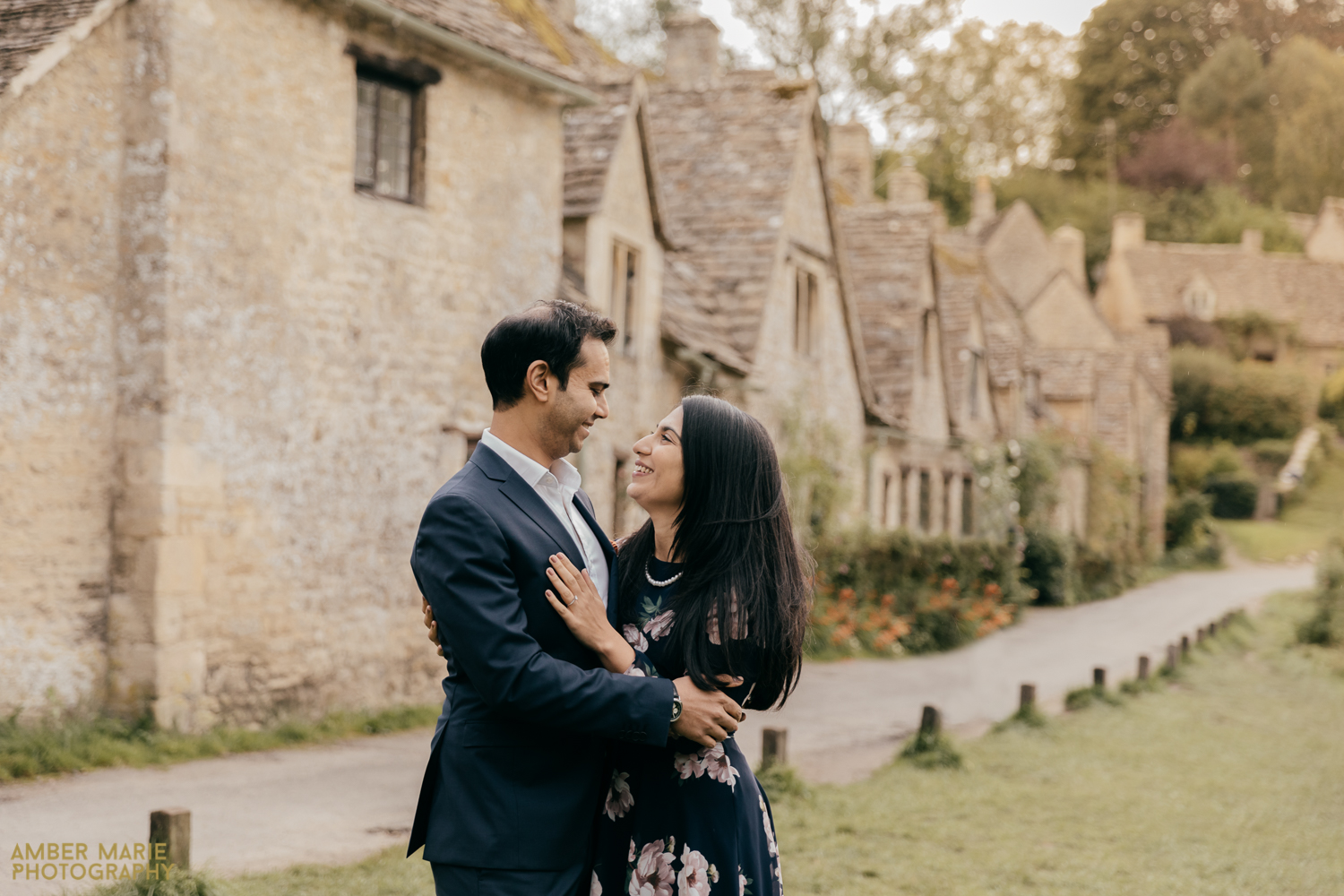 A relaxed portrait of a bride and groom during golden hour. Hugging in front of a row of quaint cottages in The Cotswolds.