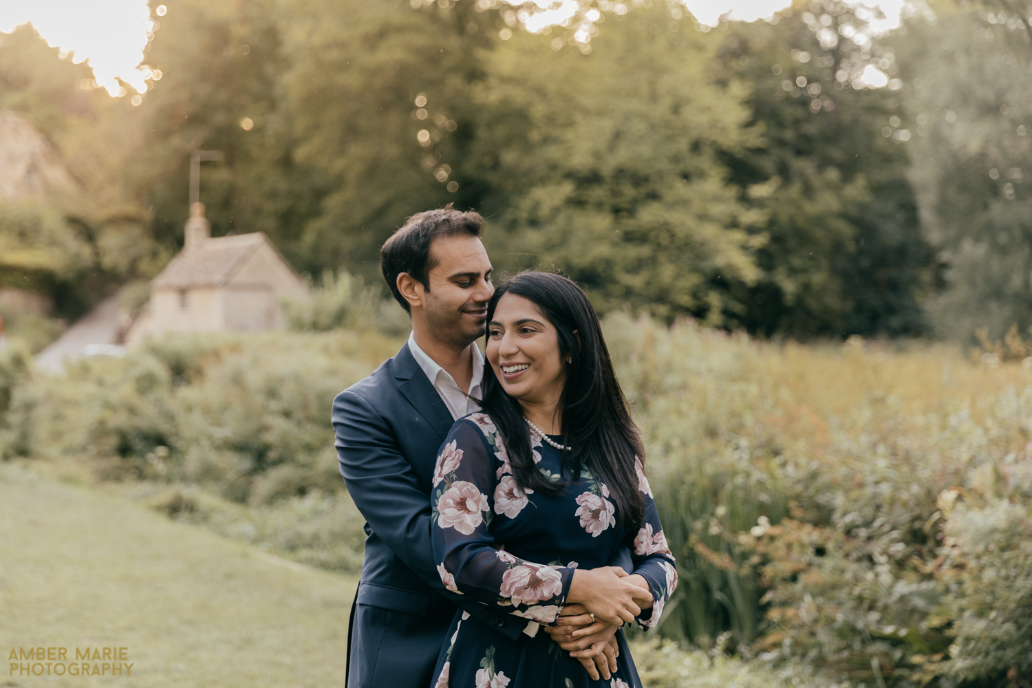A relaxed wedding portrait of a couple. The groom is wrapping his arms around his wife as she smiles. Standing in front of a wild meadow in The Cotswolds.