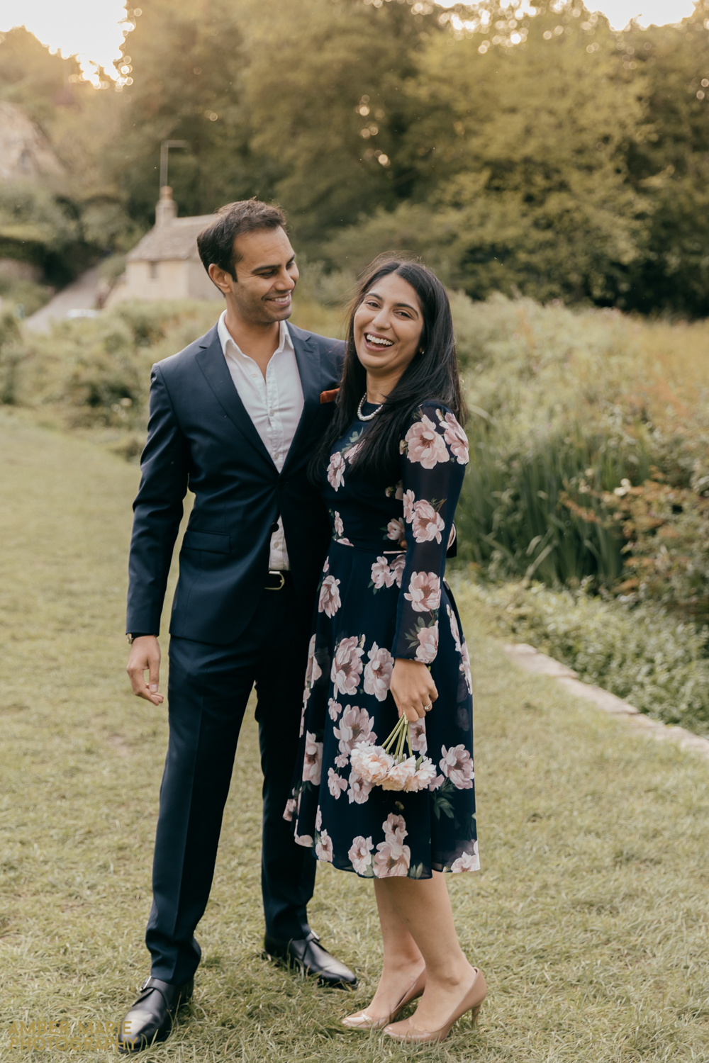 A natural portrait photograph of a joyful bride and groom. Wearing dark, relaxed wedding outfits. With a wild cotswold meadow behind them.