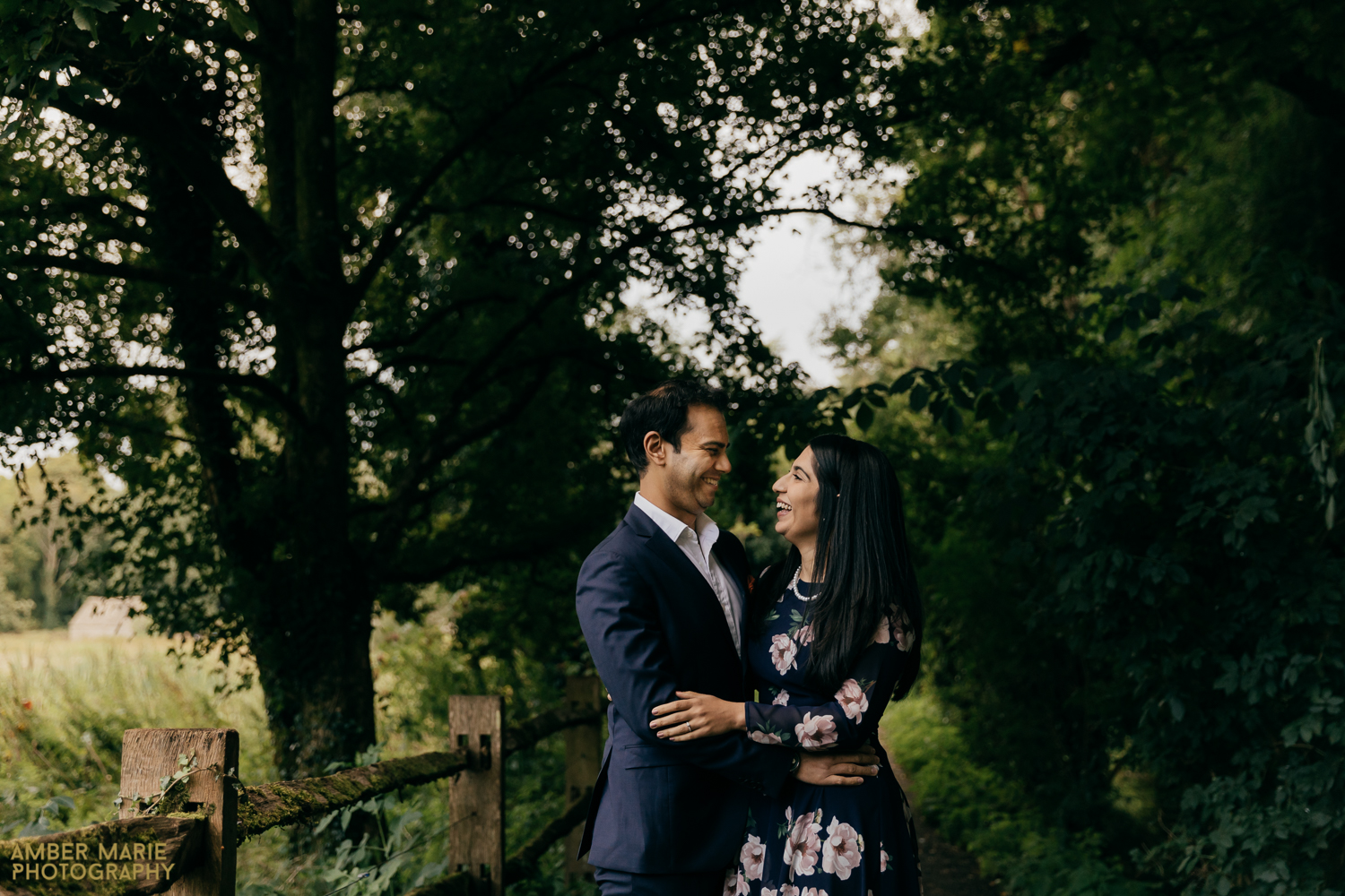 Black bride and groom hugging in a woodland, in The Cotswolds.