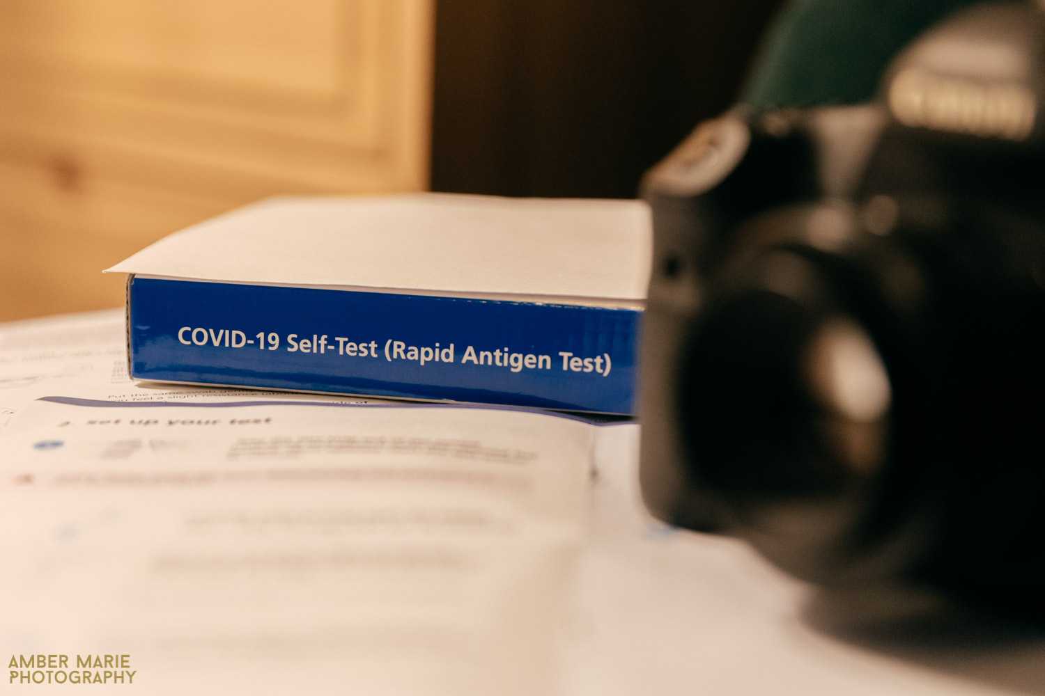 a lateral flow rapid Covid test and instructions sat next to a camera