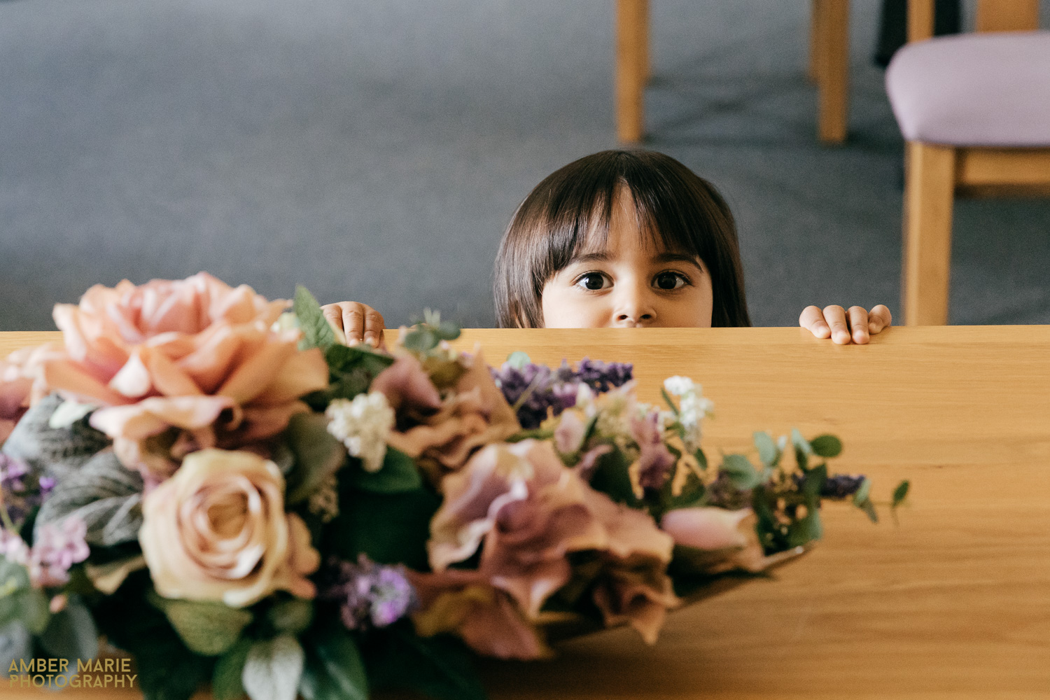 Candid photo of flower girl peeping over table