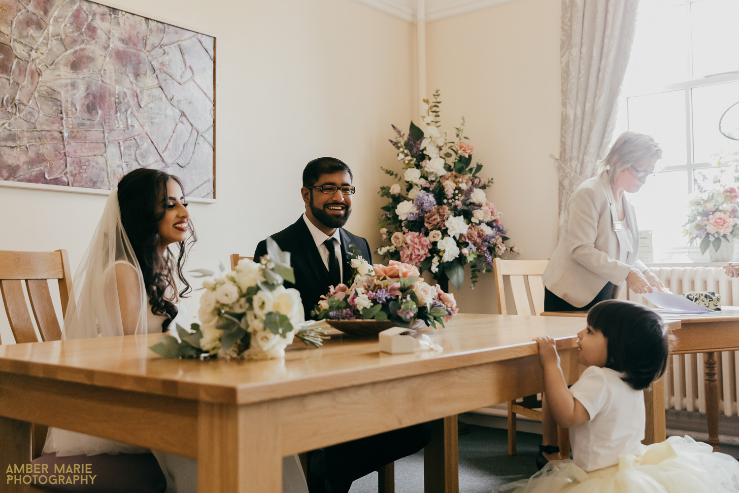 flower girl playing whilst couple sign register at micro wedding ceremony