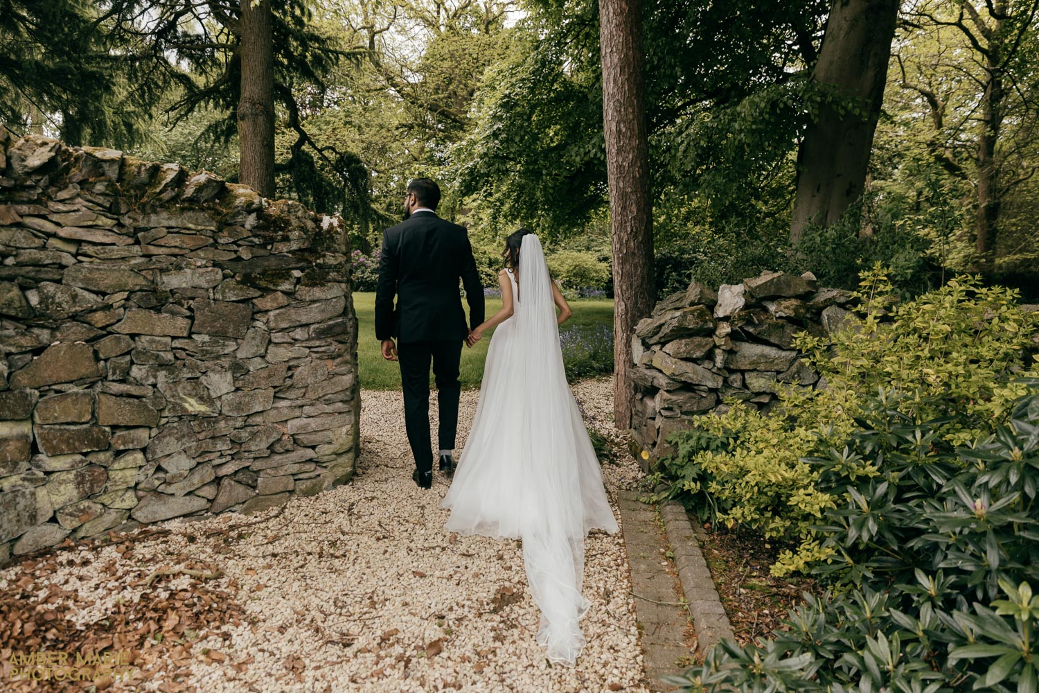 Bride and groom walking through woodland garden at Abbots Oak in Leicester