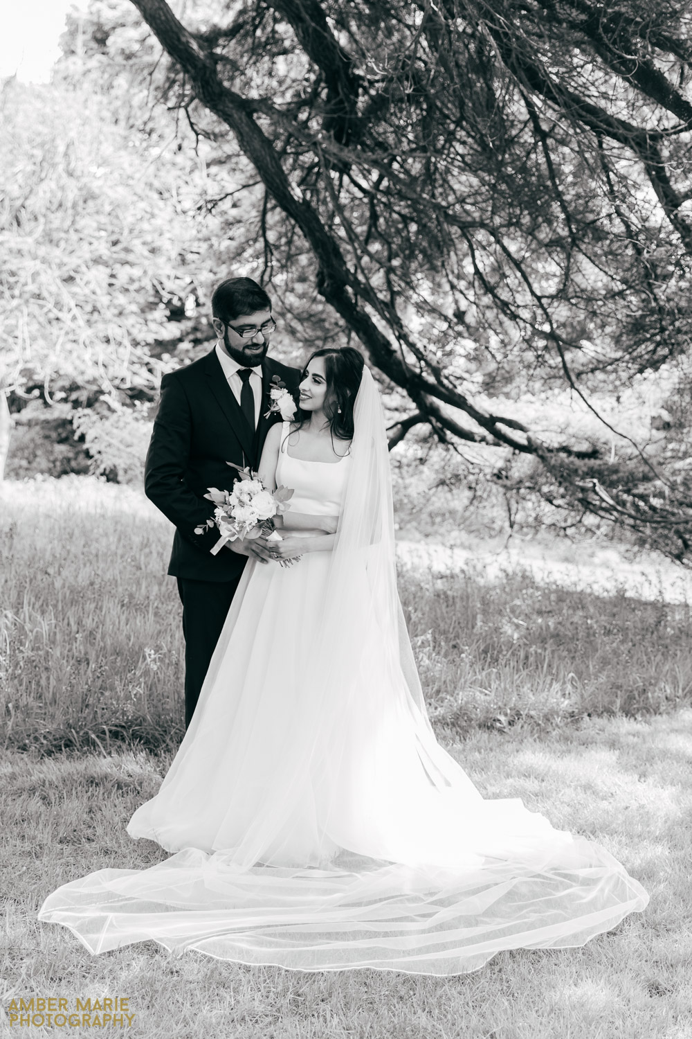Black and white portrait of happy bride and groom in Abbots Oak garden