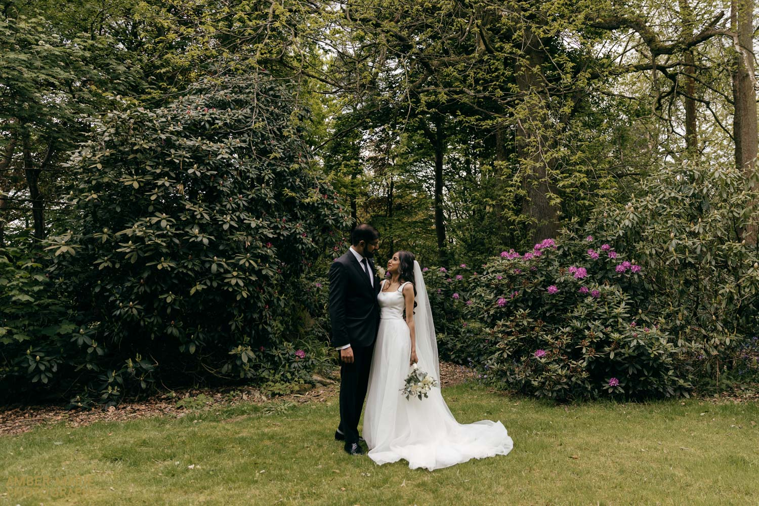 Creative wedding photo of bride and groom in woodland at Abbots Oak