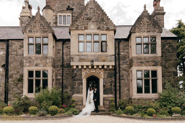 Bride and groom stood in doorway of Abbots Oak wedding reception