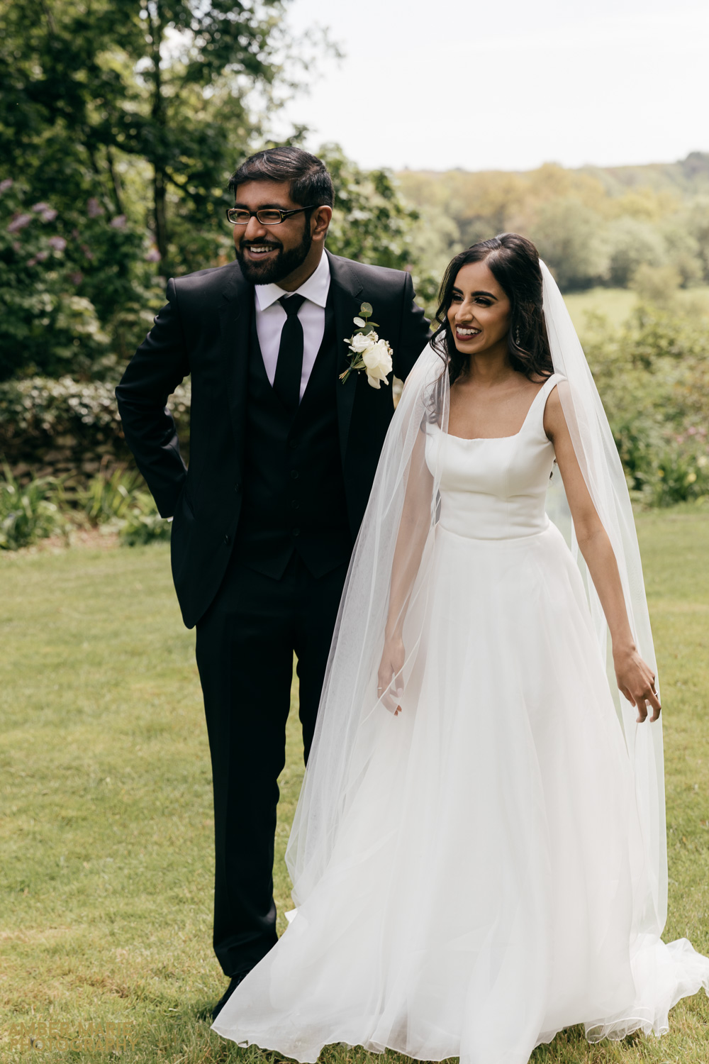 Documentary style photo of bride and groom laughing in garden