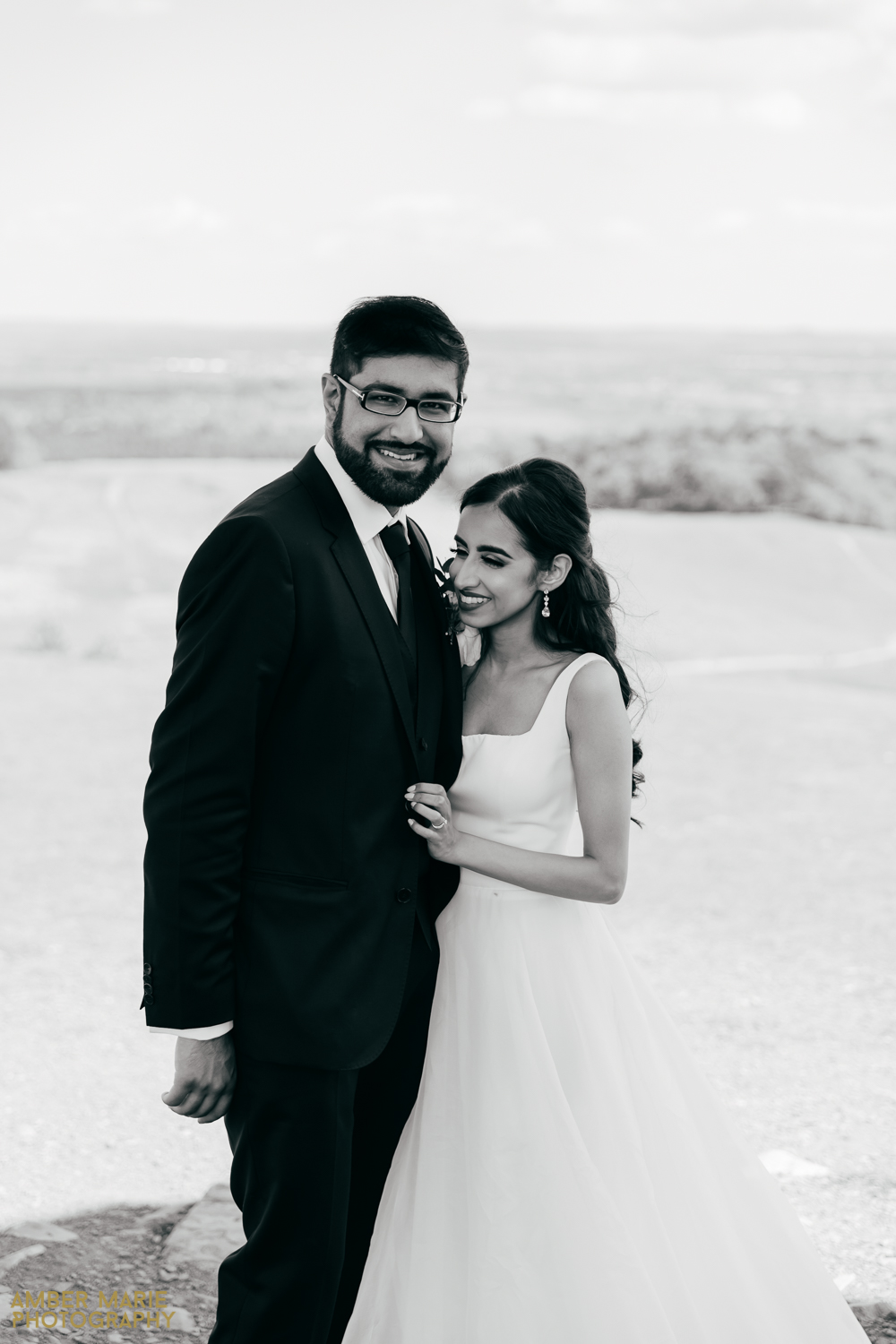 Candid black and white portrait of bride and groom in countryside