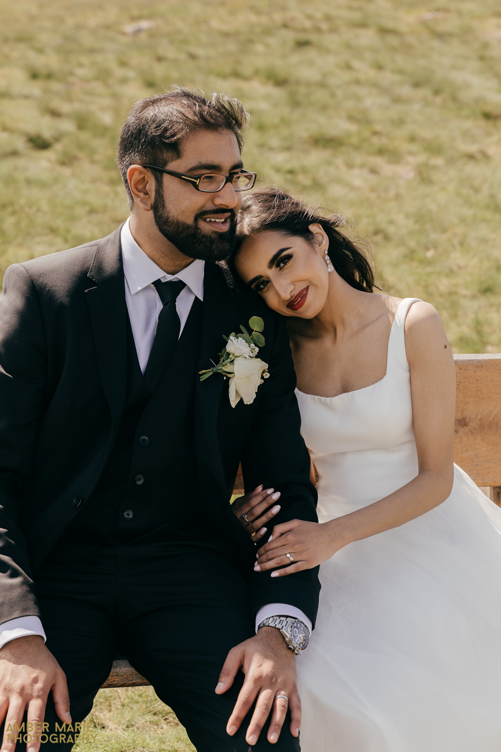 Stylish portrait of bride and groom sat on bench