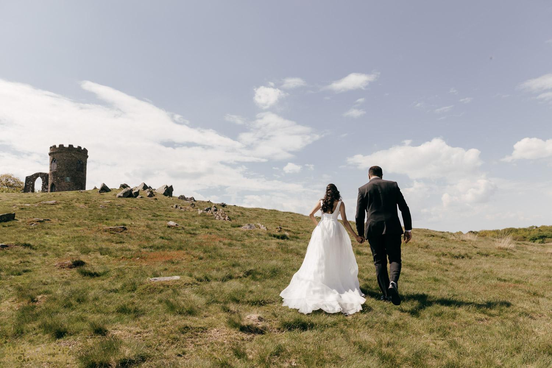 bride and groom walking holding hands in Bradgate park