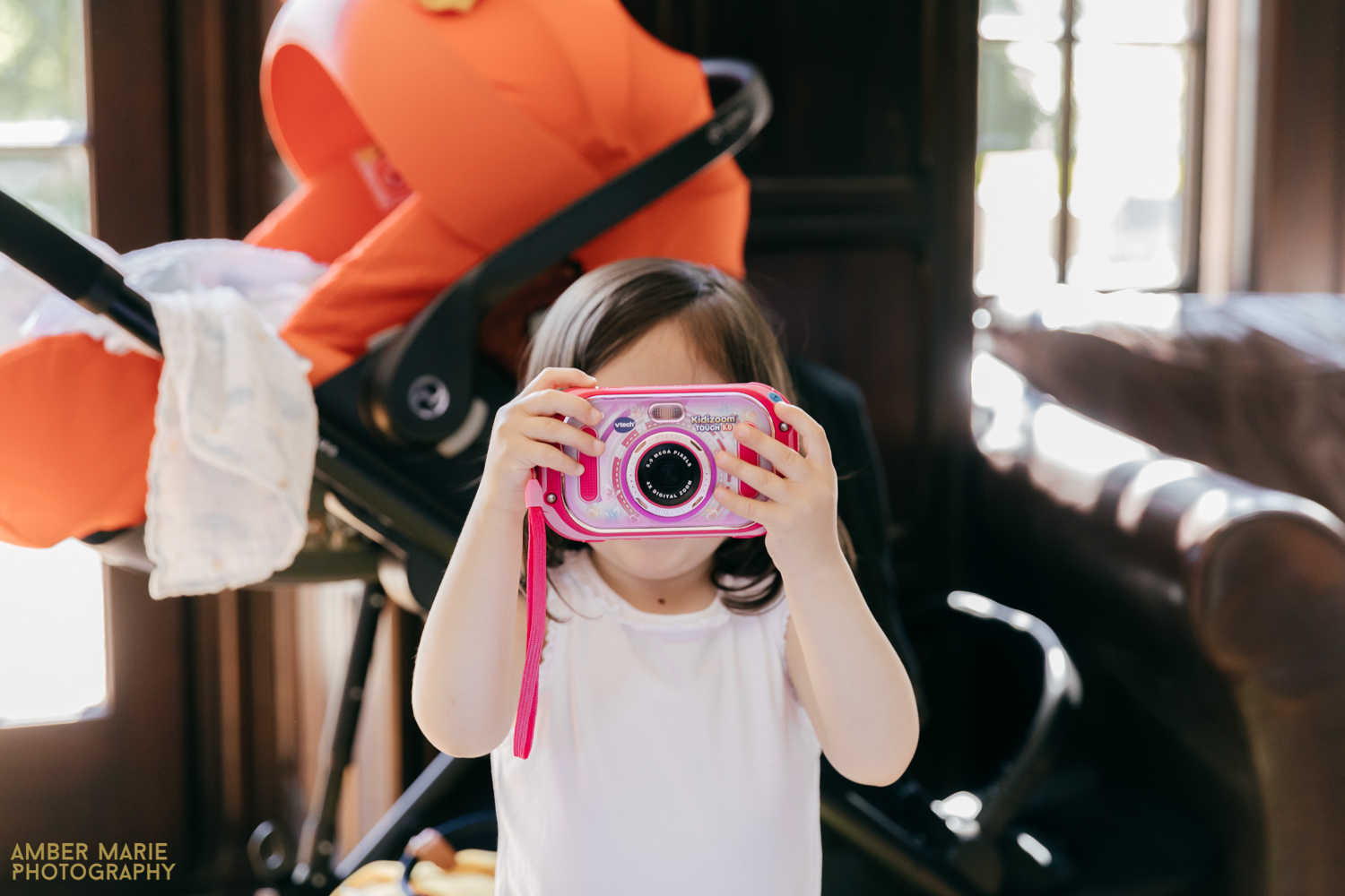Candid photo of flower girl with camera at wedding