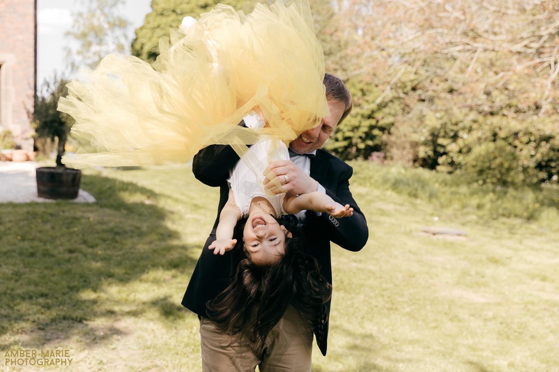 Flower girl playing at wedding in yellow tutu skirt