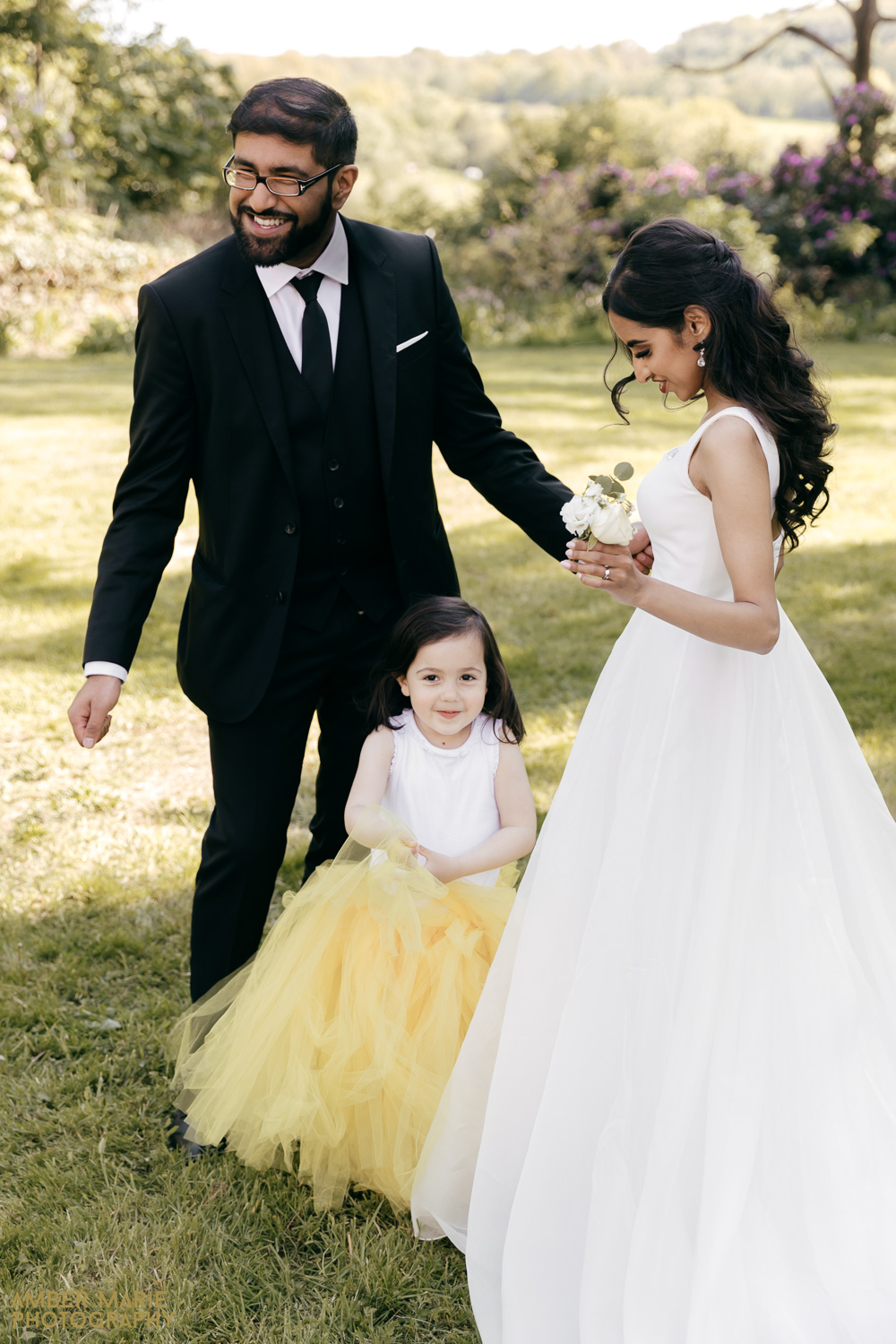 Candid wedding photo of bride and groom with flower girl in yellow
