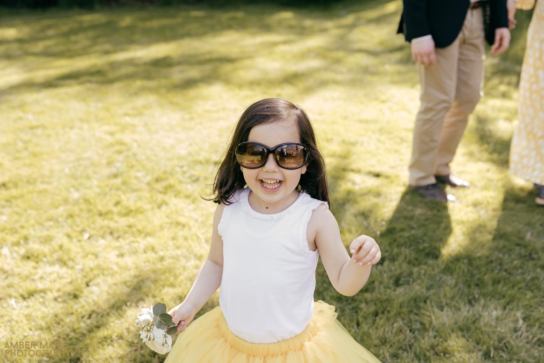 flower girl wearing big sunglasses and yellow tutu skirt