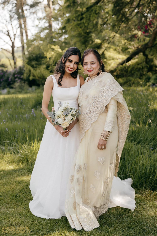 Bride in classic white wedding dress and mum wearing gold Saree dress at wedding