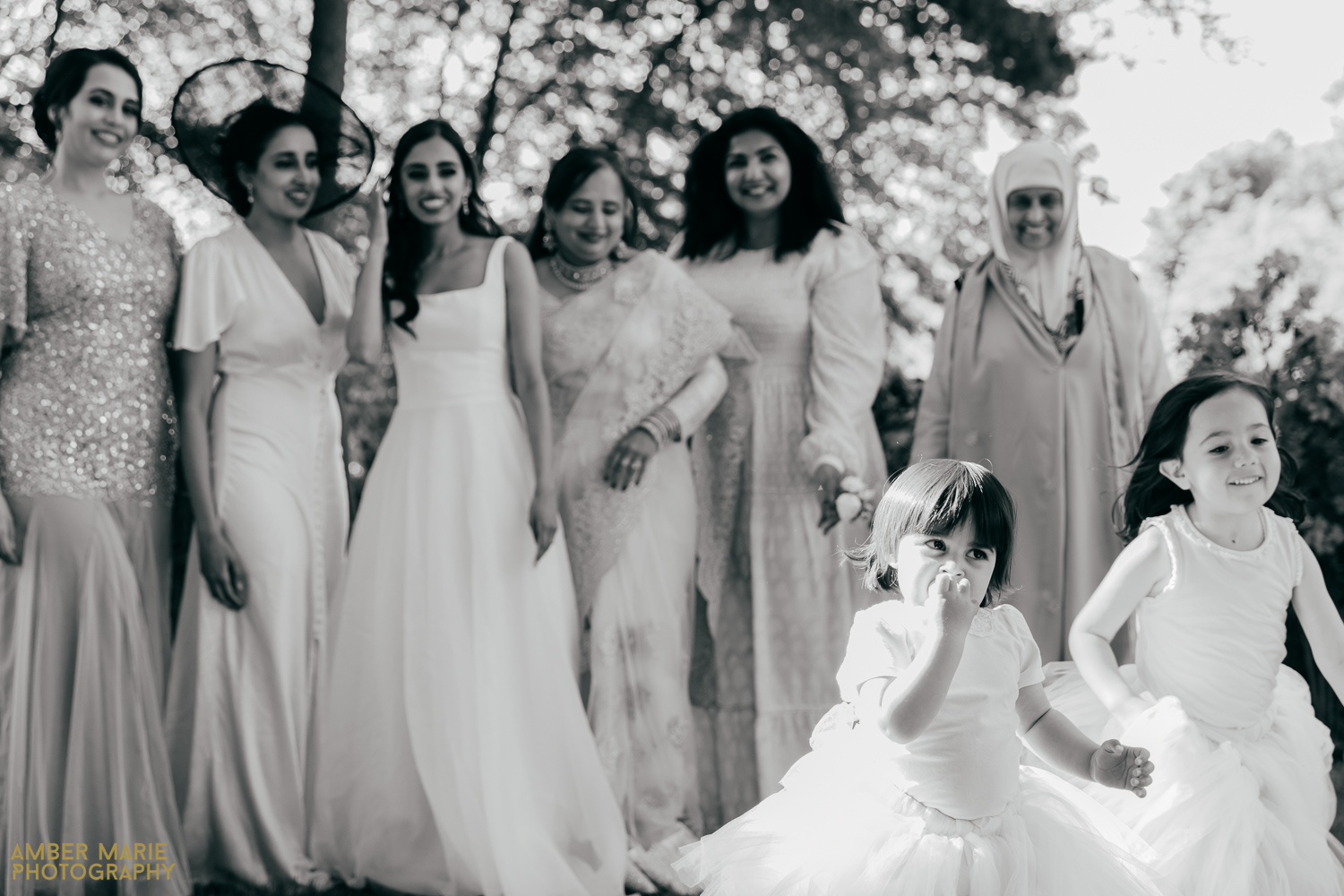 candid photo of flower girl running away from group photo at wedding