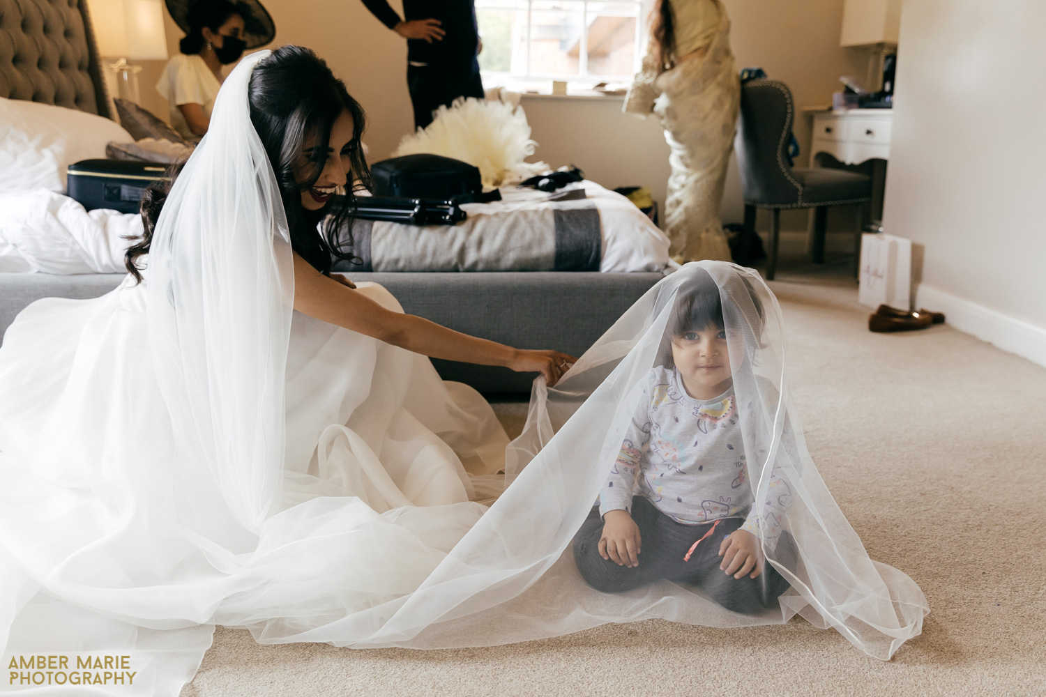 Candid wedding photo of little girl playing under brides veil