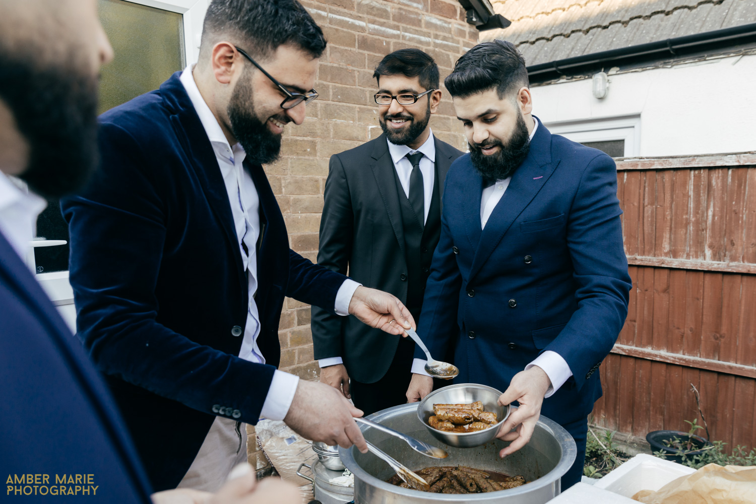 Family serving guests food at Indian wedding in garden