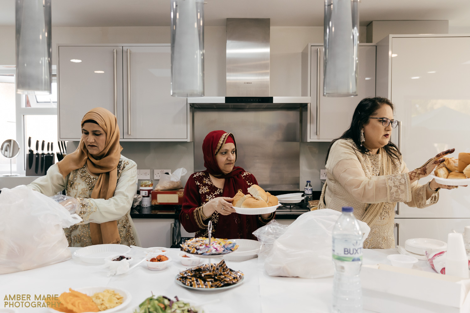 Family helping serve food in kitchen at Indian wedding reception at home