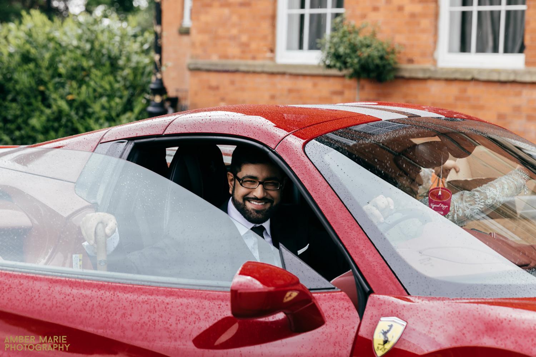natural wedding photo of groom arriving in red Ferrari