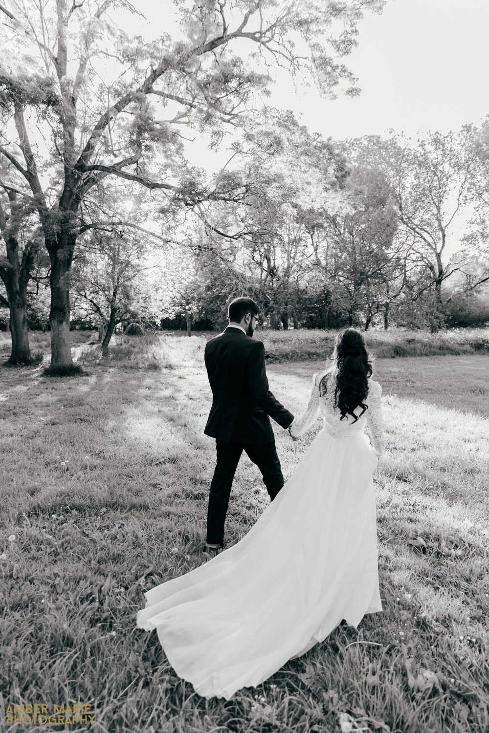 black and white photo of bride and groom walking holding hands