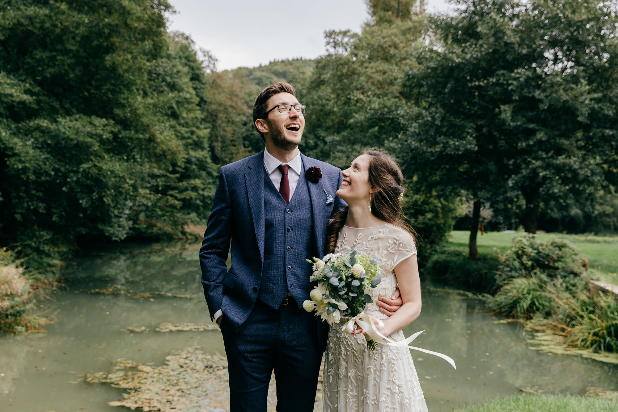 Natural Wedding Photography of laughing couple in front of lake at Owlpen Manor Wedding in The Cotswolds
