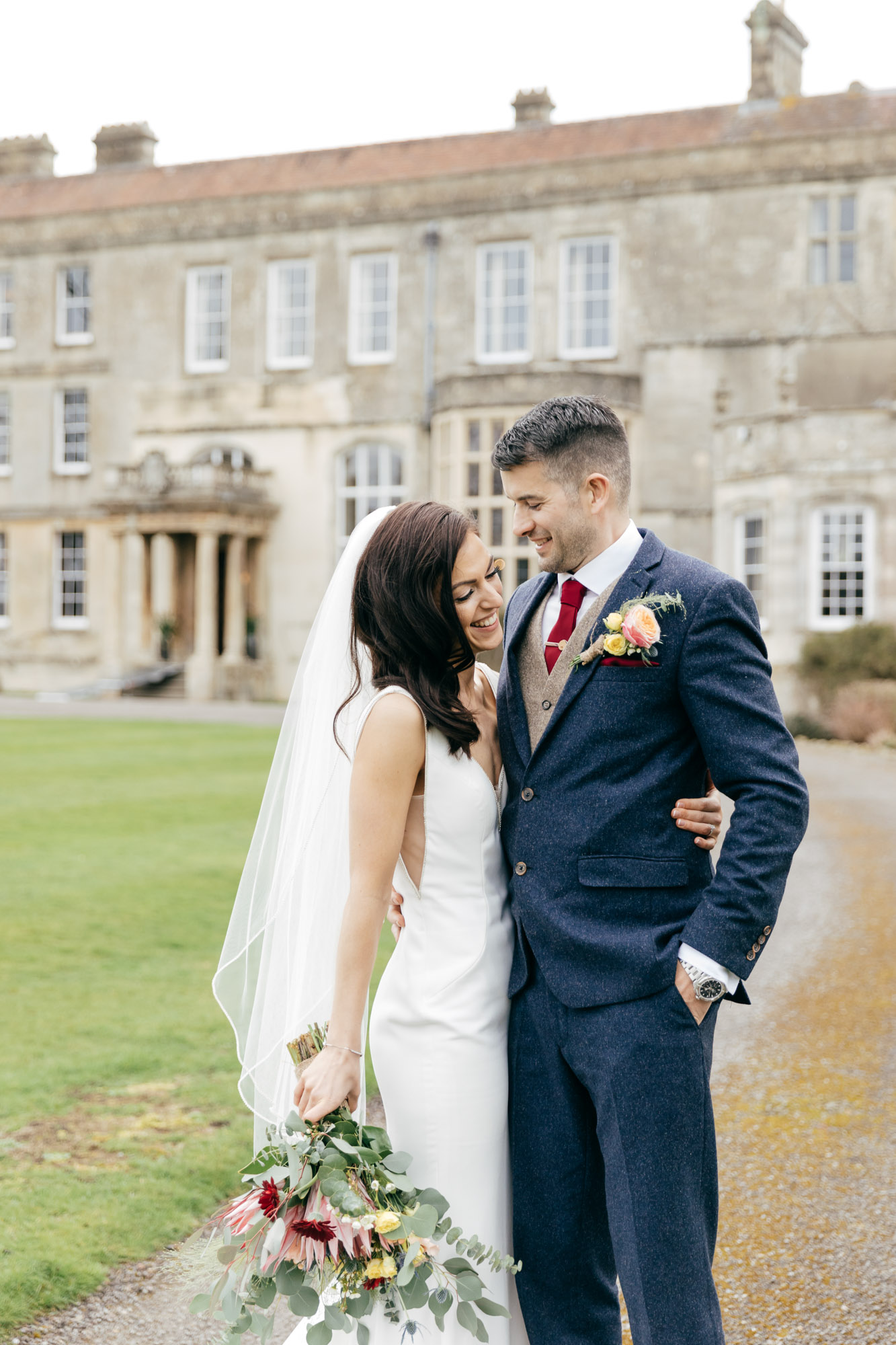 Natural wedding photography of happy couple with Elmore Court Wedding in background